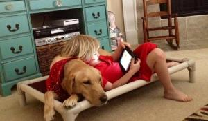 Charlie shares his Kuranda bed—and serves as a pillow—for iPad-using Lily